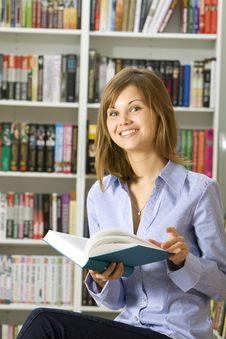 Young Woman Reading Book In The Library Royalty Free Stock Photography