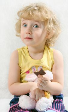 Little Blonde Curly Girl Eating Chocolate With Toy