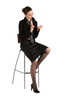 Girl In Black Suit Sits On Stool. Royalty Free Stock Photo