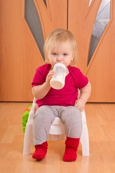 Baby Sit On Chair And Drink Milk From Bottle Royalty Free Stock Images