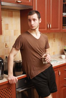 Guy In The Kitchen With Glass Of Water Royalty Free Stock Photography