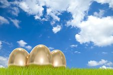 Golden Easter Eggs In Front Of A Cloudy Sky Royalty Free Stock Image
