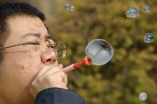 Free A Man Blowing Soap Bubbles Royalty Free Stock Images - 18355889