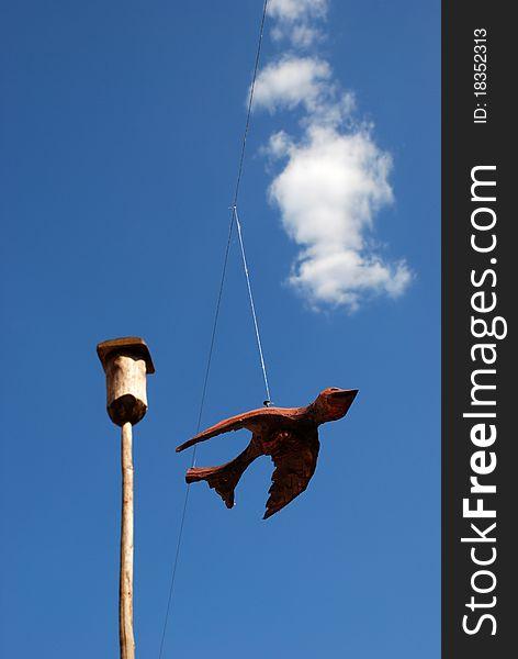 Wooden bird on blue sky