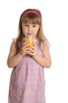 The Little Girl Drinks Orange Juice Royalty Free Stock Photography