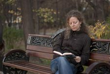 Free Curly Girl Reading In A Park Royalty Free Stock Image - 18432106