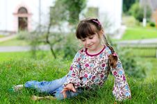 Little Girl Sits On Grass Royalty Free Stock Photos