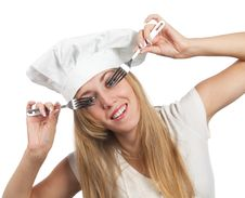 Female Chef Looking Through Forks Royalty Free Stock Photography
