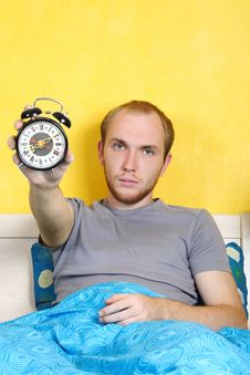 Man Lying In Bed And Showing Alarm Clock Stock Images