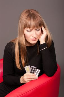 Woman With Headache And Pills Sitting On Sofa Royalty Free Stock Photos