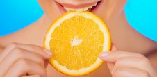 Free Woman With Relish Eating A Slice Of Orange Royalty Free Stock Photos - 18451428