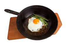 Fried Eggs On A Frying Pan On A Board Stock Photos