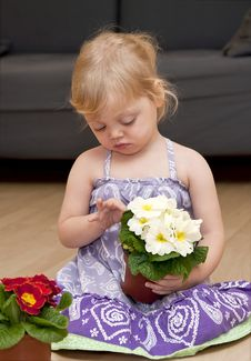 Girl Sits On The Floor And Plays With Flower
