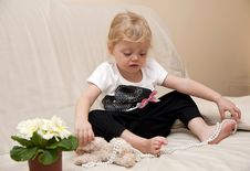 Free Girl Sitting On A Sofa And Playing With Beads Stock Photos - 18459393