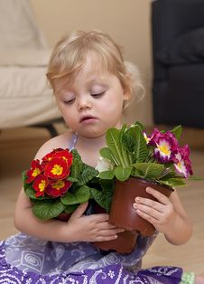 Girl Sits On The Floor And Plays With Flower Royalty Free Stock Photos