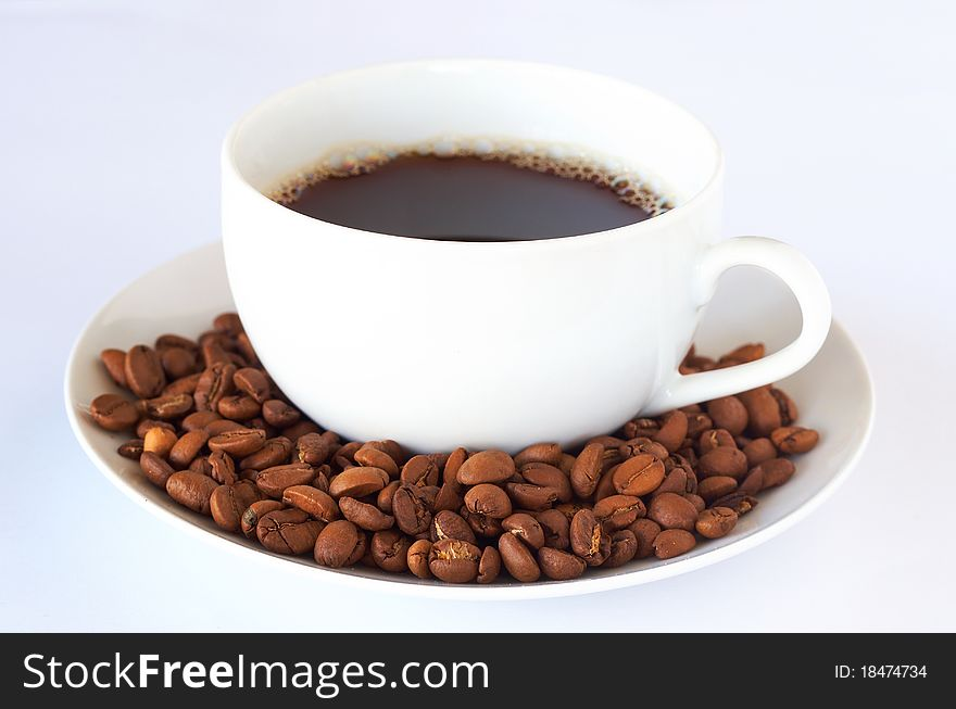 Cup of fresh coffee with roast beans