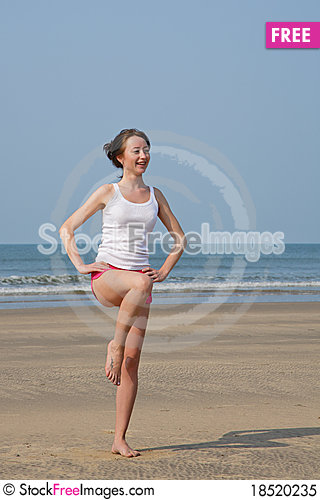 Young woman doing exercises on the beach Stock Photo