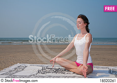 Young woman doing yoga on the beach Stock Photo