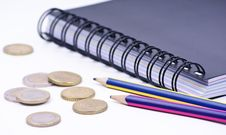 Notebook With Pencils And Coins Royalty Free Stock Images