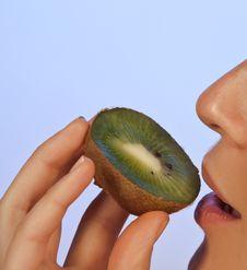 Young Woman Enjoying A Slice Of Kiwi Stock Image