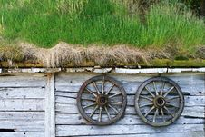 Free Spoked Wheels At A Wooden Hut Stock Images - 18629534