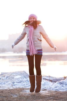 Positive Smiling Girl In Winter Clothes - Jumping Stock Image