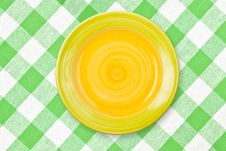 Round Yellow Plate On Green Checked Tablecloth Royalty Free Stock Photo