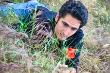 Young Man  On The Grass With Flower Royalty Free Stock Photography