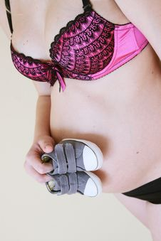 Pregnant Woman With Baby Shoes Royalty Free Stock Images