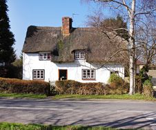Thatched Village Cottage Next To A Road Stock Image