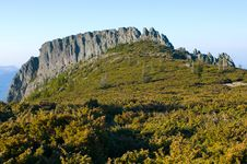 Free Rocky Cliff With Green Meadow Stock Images - 18738224