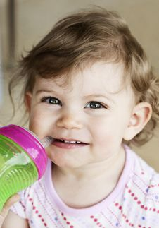 Cute Little Girl Drinking From Cup Stock Image