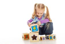 Free The Small Lovely Girl Collects Toy Cubes. Royalty Free Stock Photo - 18751195