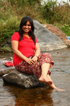 Free Indian Woman In Red Dress Sitting On A Rock Stock Image - 18779111