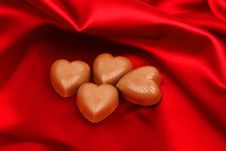 Candy Hearts On Red Satin Stock Photos
