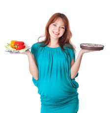 A Pregnant Smiling Woman Is Holding Food Royalty Free Stock Photography