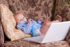 Free Serious Business Baby Near Computer On Sofa Royalty Free Stock Photography - 18789377