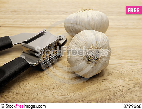 Free Garlic Press And Two Cloves Of Garlic Royalty Free Stock Photos - 18799668
