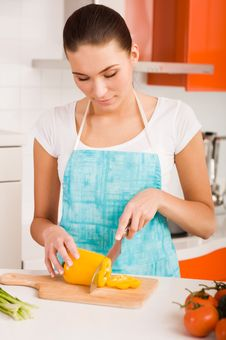 Woman Cutting Vegetables In A Kitchen Stock Photo