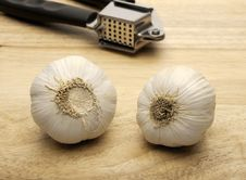 Garlic Press And Two Cloves Of Garlic Royalty Free Stock Photos