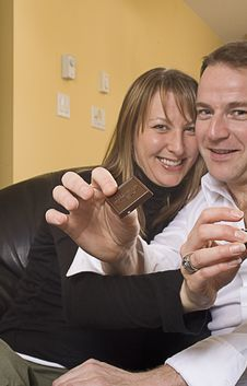 Couple On Couch Pointing Out Chocolate Stock Image