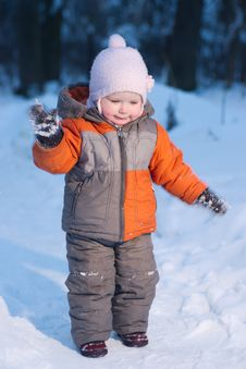 Adorable Baby Try To Remove Snow From Mittens Stock Photography