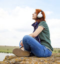Free Girl With Headphones At Rock Near Lake. Stock Photo - 18814420