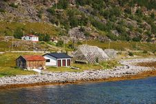 Norwegian Shore With Wooden Rack For Drying Cod Royalty Free Stock Photo
