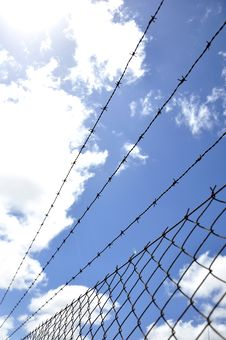 Fence With Barbed Wire Under Blue Sky Stock Image