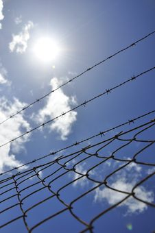 Fence With Barbed Wire Under Blue Sky