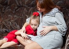 A Pregnant Woman With Her Daughter On The Sofa Stock Photo