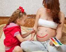 Free A Daughter Is Painting On Her Mother`s Belly Royalty Free Stock Image - 18898266