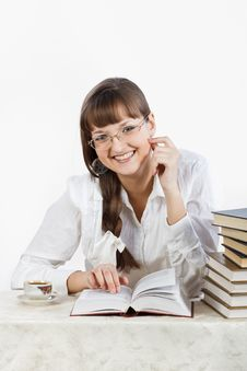 Beautiful Smiling Girl Reading A Book At The Table Royalty Free Stock Photo