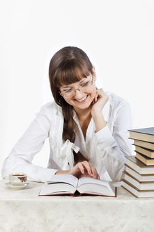Beautiful Smiling Girl Reading A Book At The Table Royalty Free Stock Photos